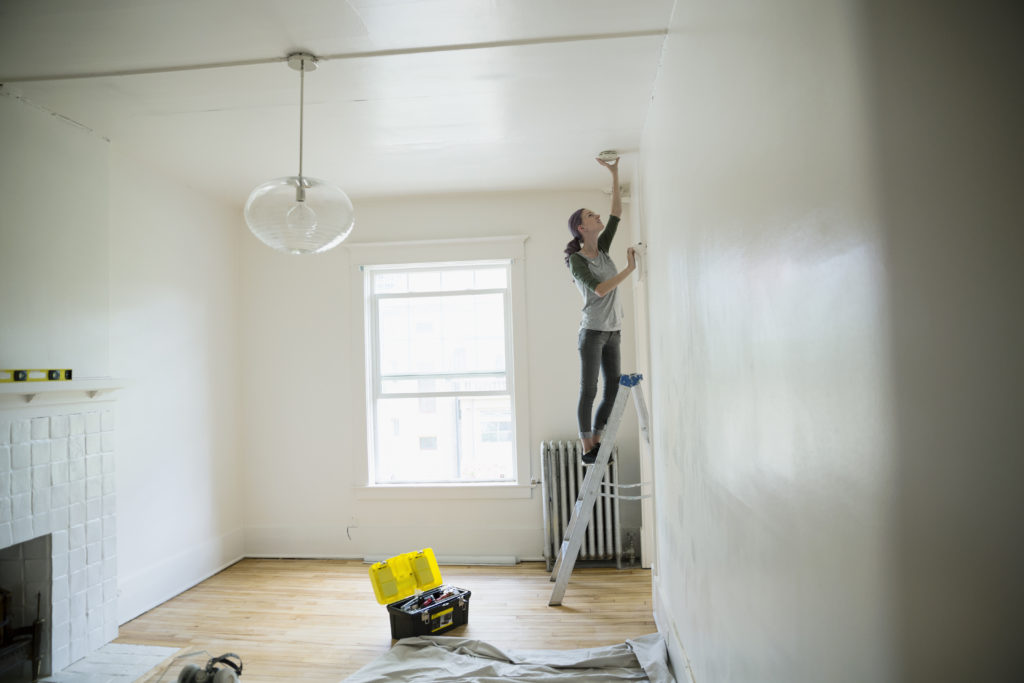 Woman on ladder testing smoke detector on ceiling